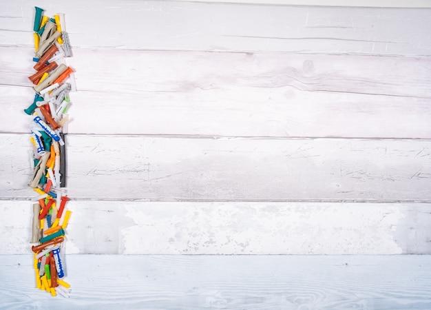 Satz verschiedene dübel für holz, beton, gips auf einem alten hölzernen hintergrund. draufsicht