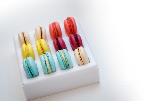 Satz verschiedene französische plätzchenmakronen makronen in einer schachtel. ansicht von oben. kaffee, schokolade, vanille, zitrone, himbeere, erdbeere, pistazie, veilchen, rose, orange schmeckt nach makronen