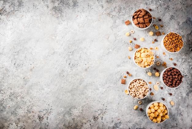 Satz verschiedene frühstückskost aus getreide corn flakes, hauche, knalle, draufsicht des grauen steintabellen-kopienraumes
