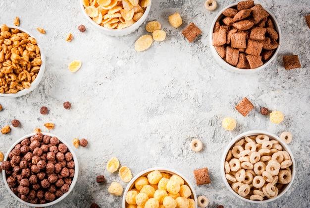 Satz verschiedene frühstückskost aus getreide corn flakes, hauche, knalle, grauer draufsichtrahmen des steintabellenkopienraumes