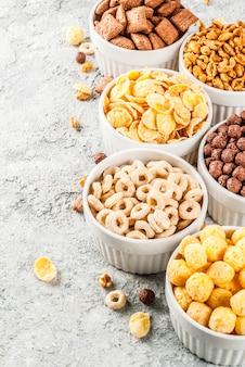Satz verschiedene frühstückskost aus getreide corn flakes, hauche, knalle, grauer steintabellen-kopienraum