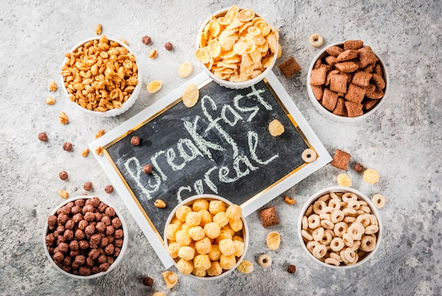 Satz verschiedene frühstückskost aus getreide corn flakes puffs knallt graue steintabelle