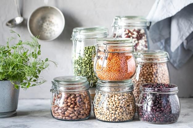 Satz verschiedene hülsenfrüchte in gläsern auf, betonweißer tisch. eine proteinquelle für vegetarier. das konzept der gesunden ernährung und lagerung von lebensmitteln.