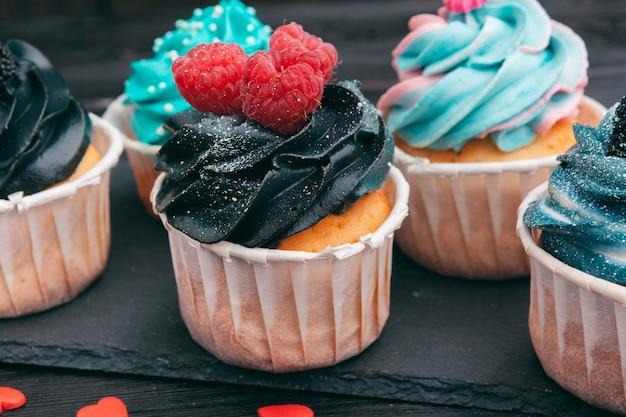Satz verschiedene köstliche kleine kuchen auf dunkelheit