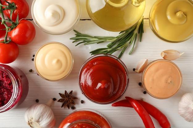 Satz verschiedene köstliche saucen, knoblauch, kirschtomaten, olivenöl auf weißem hintergrund, nahaufnahme. draufsicht