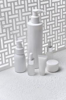 Satz verschiedene kosmetische flaschen creme oder lotion. schönheitsprodukt-mock-up gegen einen geometrischen bildschirm mit natürlichem licht und schatten. leere verpackung. natürliches beauty-spa-produktkonzept. attrappe, lehrmodell, simulation