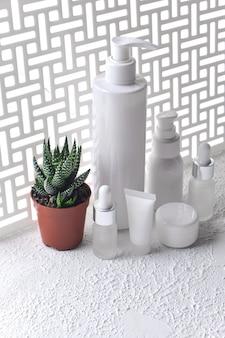 Satz verschiedene kosmetische flaschen creme oder lotion. schönheitsprodukt-mock-up gegen einen geometrischen bildschirm mit natürlichem licht und schatten. natürliches beauty-spa-produkt und ein topf mit aloe
