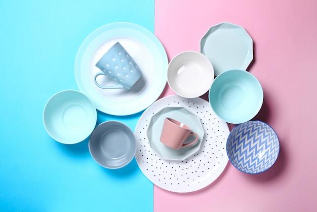 Satz verschiedene moderne weiße und blaue platten, schüsseln und schalen auf rosa und blau.