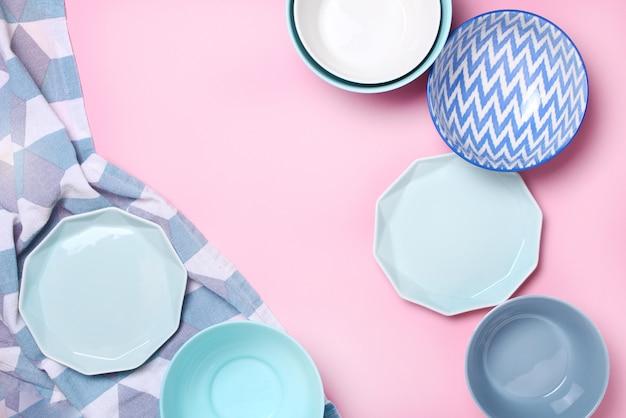 Satz verschiedene moderne weiße und blaue platten und schüsseln auf rosa