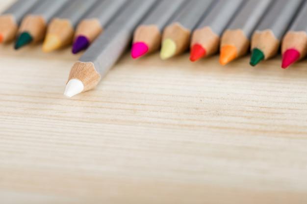 Satz verschiedenfarbige stifte auf holzschreibtisch