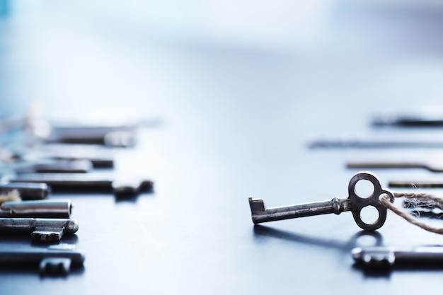 Satz vintage-schlüssel für ein schloss. retro-schlüssel auf dunklem steinhintergrund. das konzept, den weg zu wählen, um das ziel zu erreichen.