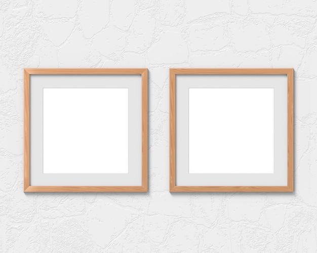 Satz von 2 quadratischen holzrahmenmodell mit einem rand, der an der wand hängt. leere basis für bild oder text. 3d-rendering.