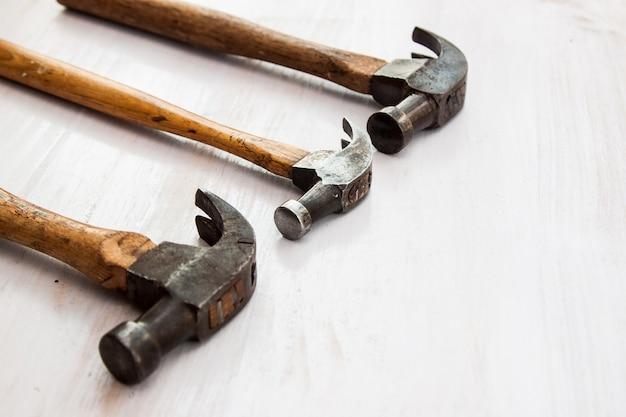 Satz von drei alten alten hammerwerkzeug hammerkopf auf dem holzfußbodenhintergrund