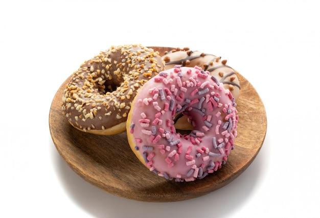 Satz von drei donuts auf einer weinlese-restaurantplatte lokalisiert auf weißem hintergrund. schokoladenbraune und rosa donut-kollektion mit bunten streuseln