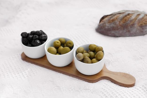 Satz von drei weißen schüsseln mit oliven auf hölzernem behälter auf weißer decke