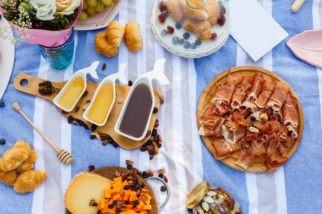 Satz von drei weißen soßenbooten mit süßem honig auf hölzernem behälter