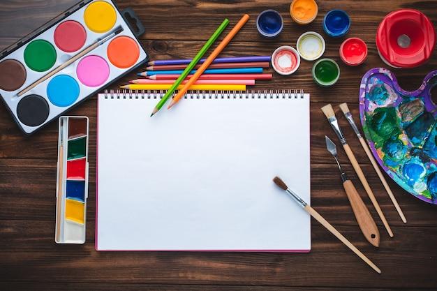 Satz von farben, bleistiften, hilfsmitteln für das malen und leeres weißes papierblatt