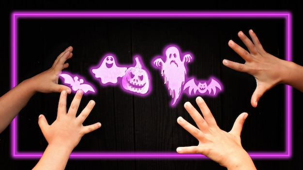 Satz von halloween-neon-halloween-symbolen für urlaubsparty. aufhellen von trendigen gruseligen kürbissen, spinnen, fledermäusen, geistern und mumien auf dunklem holzhintergrund und kinderhänden, fokus auf urlaubssymbolen