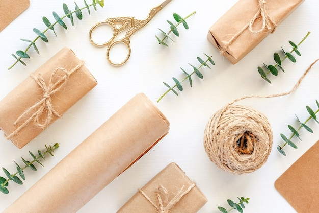 Satz von materialien zum verpacken von weihnachtsgeschenken. kraftpapier, juteschnur, schere, kisten und zweige aus grünem eukalyptus
