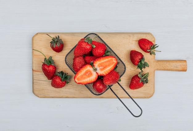 Satz von mehreren erdbeeren um ihn herum und erdbeeren in einem schwarzen korb auf einem hölzernen schneidebrett und weißem hintergrund. flach liegen.