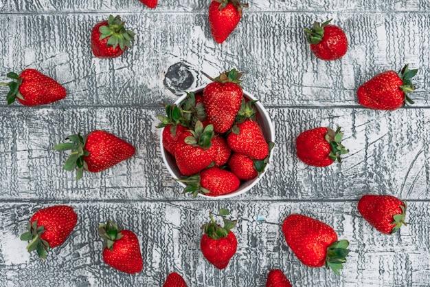 Satz von mehreren erdbeeren um ihn herum und erdbeeren in einer pappschale auf einem grauen hölzernen hintergrund. flach liegen.
