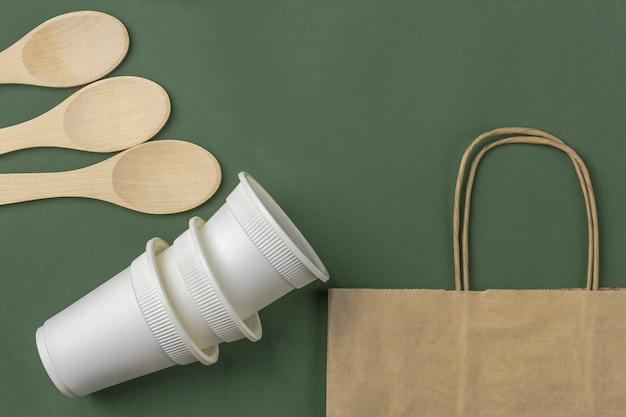 Satz von öko-tasche, biologisch abbaubare kaffeetassen aus papier, holzlöffel. null abfall, umweltfreundlich, plastikfrei.