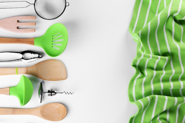 Satz von rostfreien und hölzernen utensilien mit handtuch, lokalisiert auf weiß