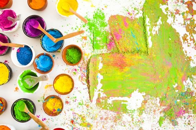 Satz von schüsseln mit hellen trockenen farben in der nähe von farbflecken