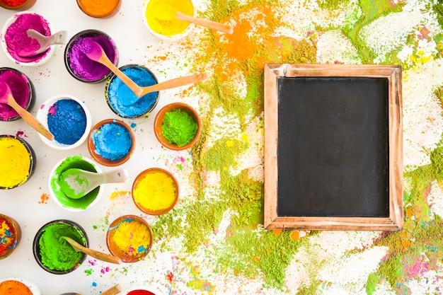 Satz von schüsseln mit hellen trockenen farben in der nähe von rahmen und farbstapeln