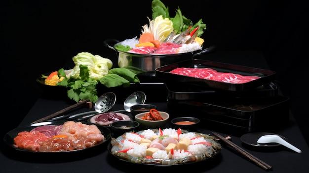 Satz von shabu shabu im heißen topf, im frischen geschnittenen fleisch, in den meeresfrüchten und im gemüse mit schwarzem hintergrund