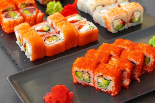 Satz von verschiedenen sushi-rollen, die auf grauem hintergrund nah oben gedient werden