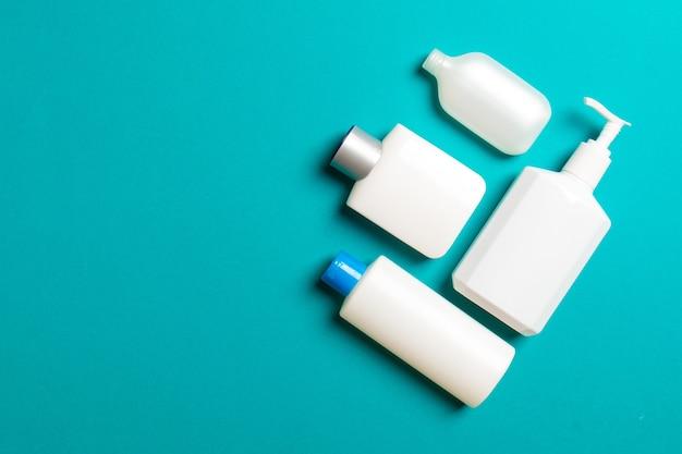 Satz von weißen kosmetischen behältern lokalisiert auf farbigem hintergrund, draufsicht mit kopienraum. gruppe von plastikflaschenbehältern mit leerem raum für ihr design.