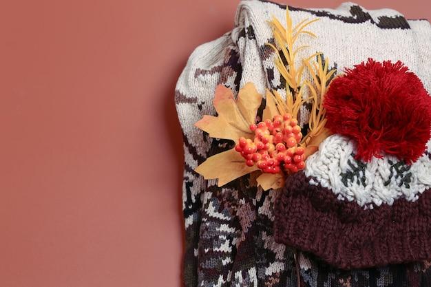 Satz warme herbstkleidung auf einem beige hintergrund, draufsicht. strickpullover und wollmütze. flacher stil und platz für text