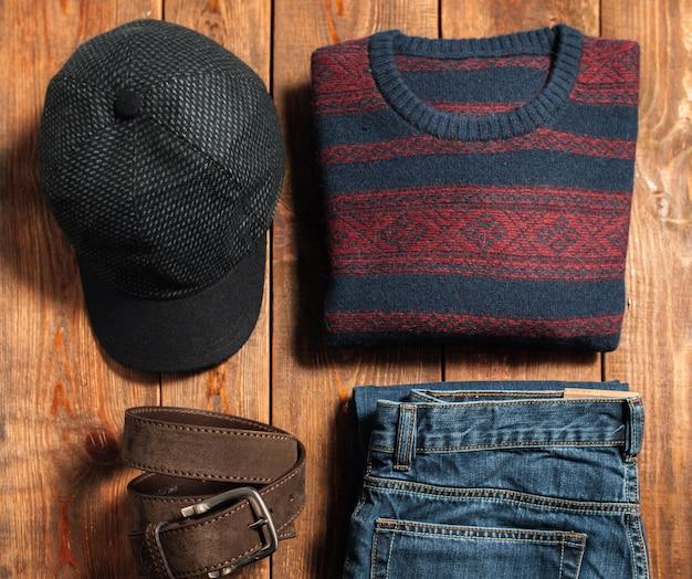 Satz warmer männlicher stoffkappenjeans-pullovergürtel auf holz