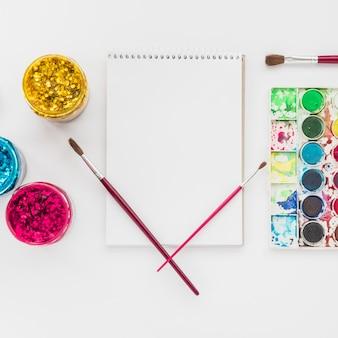 Satz wasserfarbe und funkelnfarbe mit dem gewundenen notizblock lokalisiert auf weißem hintergrund