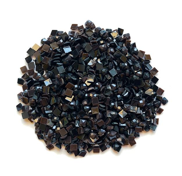 Satz weiche schwarze diamanten für diamantstickerei lokalisiert auf weißem hintergrund. hobbys und heimwerken, materialien zum erstellen von diamantstickereien.