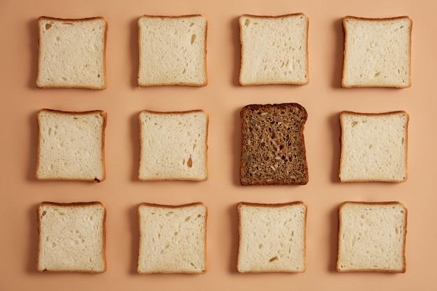 Satz weiß- und vollkornbrotscheiben auf hellbeigem hintergrund. rechteckige brotstücke aus bio-mehl, eines ist dunkel zum toasten vorbereitet. draufsicht von oben, flach gelegen. gebäck.