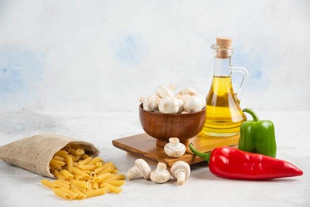 Satz weiße champignons, pasta, chilischoten und natives olivenöl extra auf dem marmor.