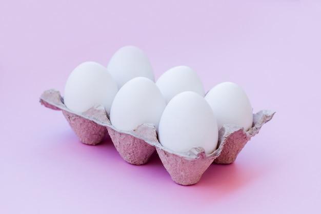Satz weiße eier auf einem rosa hintergrund