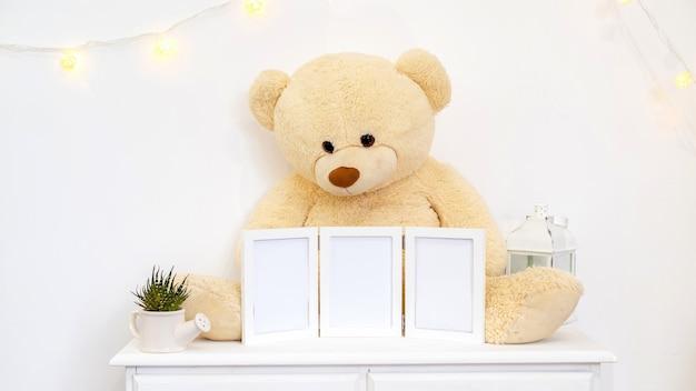 Satz weiße hauptdekorationen mit teddybär, fotorahmen und kerzen