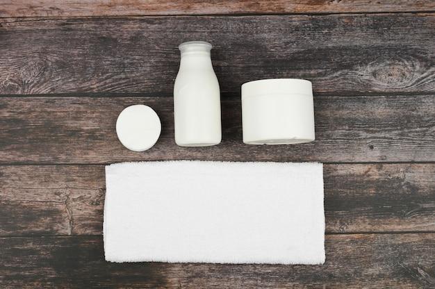 Satz weiße kosmetikbehälter auf hölzernem raum, draufsicht mit kopierraum. markenverpackungsmodell