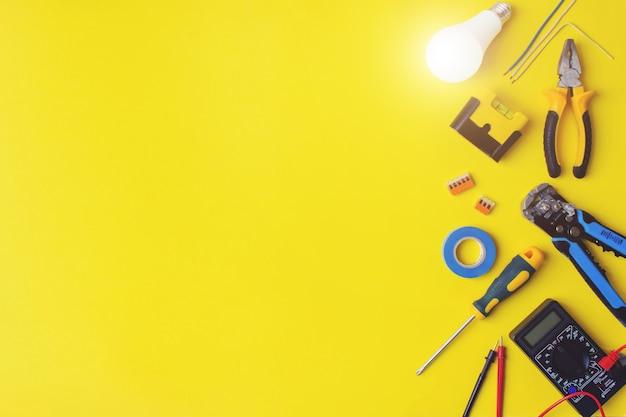 Satz werkzeuge des elektrikers auf gelbem hintergrund. flacher aufbau mit elektrikerwerkzeugen