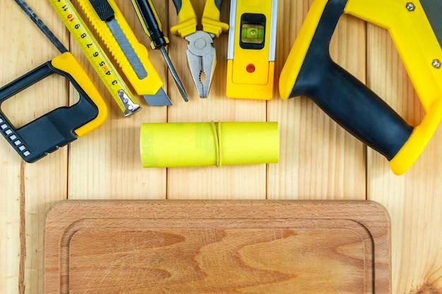 Satz werkzeuge für den baumeister auf einem hölzernen hintergrund mit einem platz für werbung.