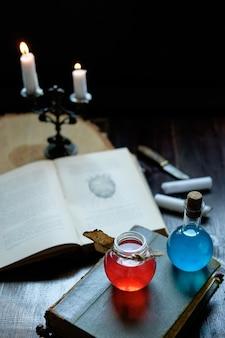 Satz zauberbuch, zaubertränke und kerzen auf dem tisch