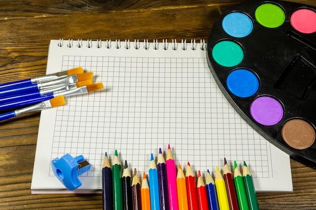 Satz zeichenwerkzeuge auf hölzernem hintergrund. leeres notizbuch, aquarellfarben, pinsel, farbstifte auf dem schreibtisch