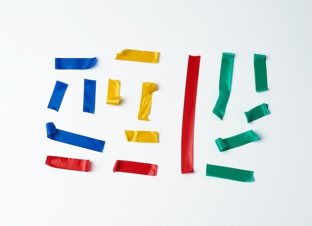Satz zerrissene mehrfarbige gummistücke des isolierbands geklebt an einer weißen oberfläche