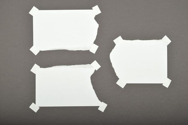 Satz zerrissene, zerrissene papierblätter mit aufklebern, die auf grauem hintergrund isoliert sind