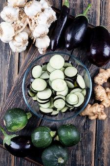 Satz zucchini, knoblauch, ingwer und geschnittene auberginen in einer schüssel auf einem holztisch. draufsicht.