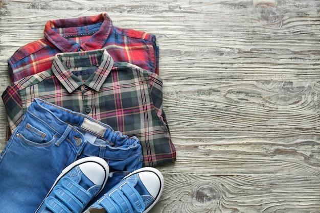 Saubere kinderkleidung mit schuhen auf dem tisch