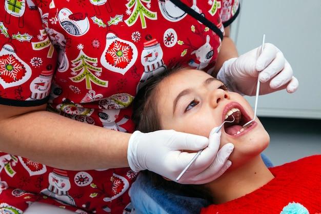 Saubere klinik des kleinen mädchens der behandlungsbürokinderzahnarztzähne jugendlich roten doktors des neuen jahres der rabattfrau ruhig bequem